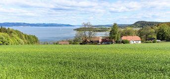 Norwegian countryside. Comprising of a farmhouse, sea and lush greens Stock Photos