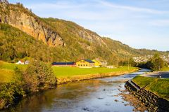 Norwegian countryside with small river and mountains. Village in rural Norway, Scandinavia Royalty Free Stock Photos