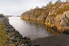 Norwegian creek in countryside. Pebble bay, a place to leave the boat on the water. Around the high cliffs. Ormdal Bay village. Aust-Agder region of southeastern Stock Photography