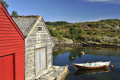 Norwegian fishing huts and lake. Scenic view of colorful fishing huts and rowing boat on lake in Norway Stock Photos