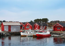Norwegian fishing village with red wooden houses. And small boats on the sea coast Stock Photos