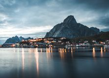Norwegian fishing village Reine at the Lofoten Islands in Norway. Dramatic sunset clouds moving over steep mountain royalty free stock photography