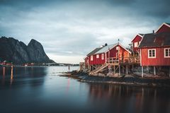 Norwegian fishing village Reine at the Lofoten Islands in Norway. Dramatic sunset clouds moving over steep mountain royalty free stock photos