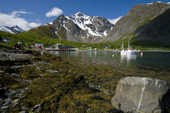 Norwegian fjord. Scenic view of Norwegian fjord with boats and village in background, Lyngenfjord, Troms, Norway royalty free stock photo