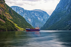 Norwegian fjord surrounded by mountains with sailing ship in a cloud summer day horizontal frame Stock Images