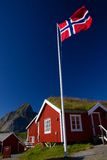 Norwegian flag. With typical norwegian red wooden house with sod roof on Lofoten islands Stock Images
