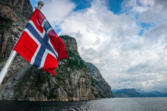 Norwegian flag against fjord mountains. The flag flow on the cruise in Norwegian fjord Stock Photography