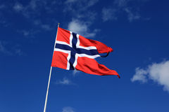 A Norwegian flag blowing in the wind against blue sky with cloud. S Stock Photography