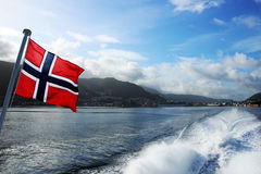 Norwegian flag floating in the air. In the back of the ferry, leaving the town and hills behind Royalty Free Stock Photo