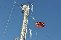 Norwegian flag flying on a mast. Of a ferry boat, photographed against blue sky royalty free stock images
