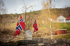 Norwegian flag with green forest landscape background. Norway symbol. Stock Photo