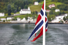Norwegian flag. Norway fjord landscape with green hill and house Royalty Free Stock Photography