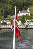 Norwegian flag. Norway fjord landscape with green hill and house Royalty Free Stock Images