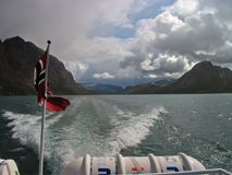 Norwegian flag on a stern of a boat. Sailing through Gjende lake. Jotunheimen national park, Norway Stock Photo