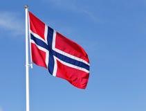 Norwegian flag. A sun lit Norwegian flag hoisted against the blue sky Royalty Free Stock Image