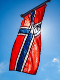 Norwegian flag up close, towards the sun. On beautiful blue sky Royalty Free Stock Photography
