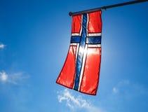 Norwegian flag up close, towards the sun. On beautiful blue sky stock image