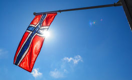 Norwegian flag up close, towards the sun. On beautiful blue sky stock images