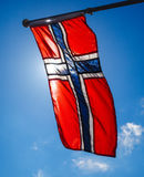 Norwegian flag up close, towards the sun. On beautiful blue sky Royalty Free Stock Image