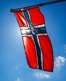 Norwegian flag up close, towards the sun. On beautiful blue sky royalty free stock image