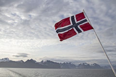 Norwegian flag. Views of the Lofoten wall from the car ferry to Bodo royalty free stock photos