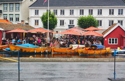 Norwegian Harbor. Tourists in the cafeteria. Traditional boats m Royalty Free Stock Photo