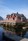 Norwegian house. Wooden norwegian house reflected into the water of a fjord Stock Image