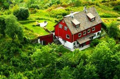 Norwegian house. Colorful rural Norwegian detached house surrounded by lush vegetation seen from above royalty free stock images