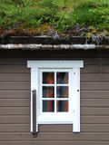 Norwegian house with grass on the roof. White window in a building with grass on its roof Royalty Free Stock Photography