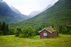 Norwegian house and mountains. Scenic view of traditional Norwegian house in green countryside with mountains in background; Norway Stock Image
