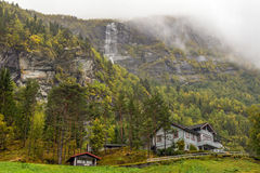 Norwegian house with waterfall in the mist Royalty Free Stock Photo