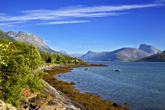 Norwegian landscape. Fishing small house on the bank of mountain lake Royalty Free Stock Images