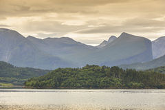 Norwegian landscape with fjord, forest and mountains at sunset. Royalty Free Stock Photography