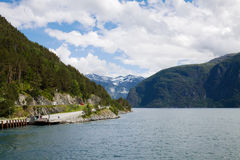 A Norwegian landscape with a fjord. A road goes to a quay from which ships sail royalty free stock photos