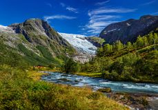 Norwegian landscape with milky blue glacier river, glacier and green mountains. Norway. Norwegian landscape with milky blue glacier river, glacier and green stock image