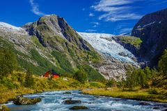 Norwegian landscape with milky blue glacier river, glacier and green mountains. Norway. Norwegian landscape with milky blue glacier river, glacier and green royalty free stock photography