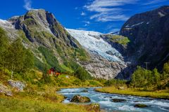 Norwegian landscape with milky blue glacier river, glacier and green mountains. Norway. Norwegian landscape with milky blue glacier river, glacier and green stock photography