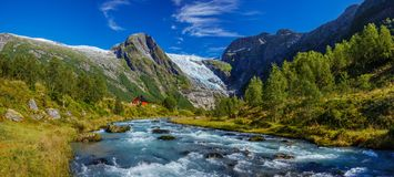 Norwegian landscape with milky blue glacier river, glacier and green mountains. Norway. Norwegian landscape with milky blue glacier river, glacier and green royalty free stock photo