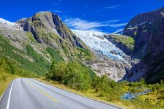 Norwegian landscape with road, glacier and green mountains. Norway. Norwegian landscape with road, glacier and green mountains. Briksdal or Briksdalsbreen stock photo