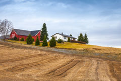 Norwegian landscape with wooden houses and empty field Royalty Free Stock Photo