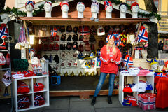 Norwegian merchandise shop and young girl (II). A young Norwegian girl sells national flags and all kinds of caps and scarfs with Scandinavian flags and colours Stock Photo