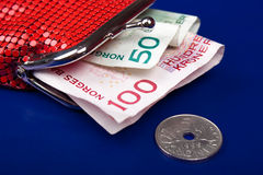 Norwegian money in a purse. Norwegian money in a red women purse on a blue background. Colours of the norwegian flag Royalty Free Stock Images