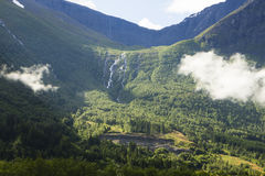 Norwegian mountain with forest and waterfalls. Beautiful green mountain wall in Norway Stock Images