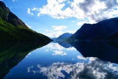 Norwegian mountains reflecting in a lake. stock photo