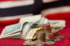 Norwegian National Currency. Norwegian banknotes and coins in front of the national flag of Norway. The flag is there to illustrate which country the currency Stock Photos