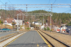 Norwegian railway platform. Drangedal, Norway, March 21, 2015: Railway Tracks and asphalt railway platform in a small town.. Early spring Royalty Free Stock Photography