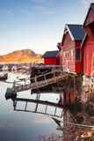 Norwegian red wooden fishinf barns. Vertical photo of Norwegian red wooden barns standing on the sea coast. Snillfjord, Sor-Trondelag region, Vingvagen fishing Royalty Free Stock Photos