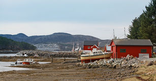 Norwegian red wooden houses and small fishing boats on the coast Royalty Free Stock Photography