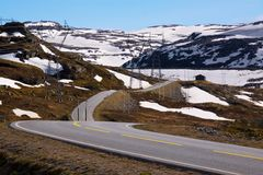 Norwegian road in spring. Road number 50 in Norway near Sognefjellet with powerlines leading above Stock Image