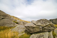 Norwegian rocks. Massive rocks and yellow grass, typical Norwegian sight, cloudy sky can be used as a copy space Stock Photos